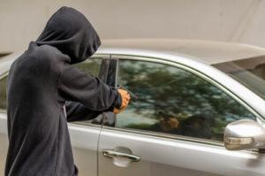 person pointing gun at vehicle